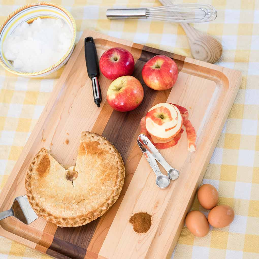 Apples peeled and an apple tart on a striped designer cutting board