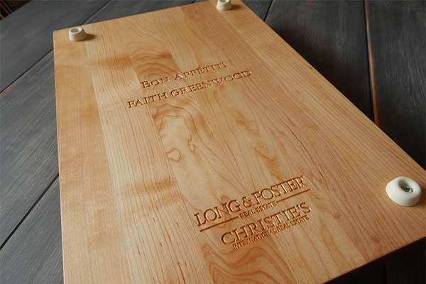 Long & Foster on teh back of a personalized cutting board with rubber feet
