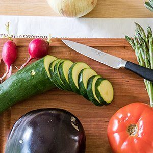 Various vegetables cut on a cutting board, including zucchini, radishes and eggplant